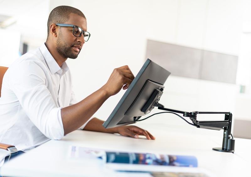 Man using Novus Clu monitor arm